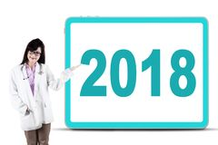 Female doctor showing a board with numbers 2018. Portrait of beautiful female doctor smiling at the camera while showing a board with numbers 2018, isolated on Stock Photos