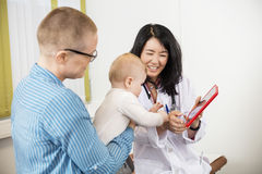 Female Doctor Showing Digital Tablet To Woman With Toddler. Happy female doctor showing digital tablet to women with toddler in clinic stock photography