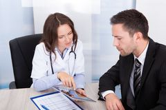 Female doctor showing digital tablet. Young Female Doctor Showing Digital Tablet To Businessman royalty free stock photography