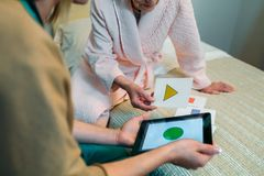 Female doctor showing geometric shapes to elderly patient. Female doctor showing geometric shape game to elderly female patient with dementia stock image
