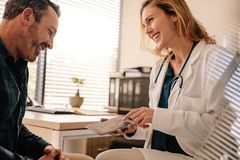 Female doctor showing good test results to a male patient royalty free stock image