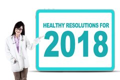 Female doctor showing healthy resolutions for 2018. Asian female doctor smiling at the camera while showing a text of healthy resolutions for 2018 on the board royalty free stock image