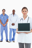 Female doctor showing laptop with colleagues. Behind her against a white background stock photography