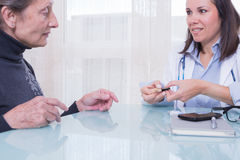 Female doctor showing patient diabetes test strips Stock Photos