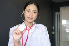 female doctor showing stethoscope for checkup at clinic. physician or medical practitioner holding stethoscope to auscultate stock image