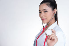 Female doctor showing stethoscope for checkup over white backgro Royalty Free Stock Images