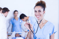 Female doctor showing stethoscope towards camera. And other doctor examining a patient behind in hospital Stock Photo
