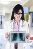 Female doctor showing x-ray on a tablet Royalty Free Stock Photography