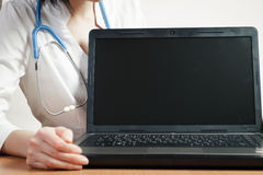 Female doctor shows laptop screen Royalty Free Stock Photos