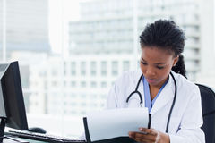 Female doctor signing a document Royalty Free Stock Photos