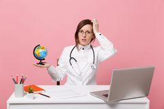 Female doctor sit at desk work on computer with medical document hold globe in hospital isolated on pastel pink wall royalty free stock photo
