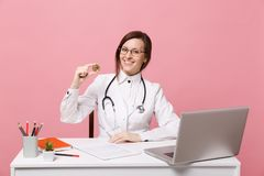 Female doctor sits at desk works on computer with medical document hold coin in hospital on pastel pink wall stock photo