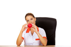 Female doctor sitting behind the desk and holding heart toy. Smile female doctor or nurse sitting behind the desk and holding heart toy royalty free stock photography