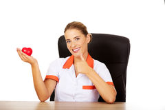 Female doctor sitting behind the desk and holding heart toy. Smile female doctor or nurse sitting behind the desk and holding heart toy royalty free stock photos