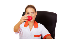 Female doctor sitting behind the desk and holding heart toy. Smile female doctor or nurse sitting behind the desk and holding heart toy royalty free stock images