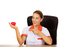 Female doctor sitting behind the desk and holding heart toy. Smile female doctor or nurse sitting behind the desk and holding heart toy stock photo