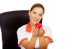 Female doctor sitting behind the desk and holding heart toy. Smile female doctor or nurse sitting behind the desk and holding heart toy stock photography