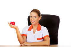 Female doctor sitting behind the desk and holding heart toy. Smile female doctor or nurse sitting behind the desk and holding heart toy stock image