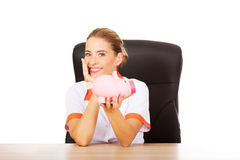 Female doctor sitting behind the desk and holding a piggybank Stock Image