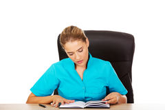 Female doctor sitting behind the desk and writing a notes Royalty Free Stock Images