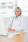 Female doctor sitting with computer at medical office Royalty Free Stock Image