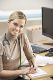Female Doctor sitting at desk Royalty Free Stock Photos