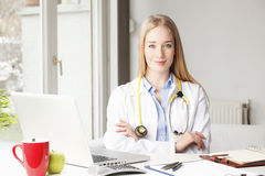 Female doctor sitting at desk in clinic. Royalty Free Stock Images