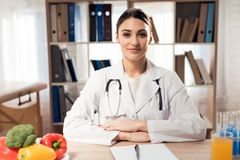 Female doctor sitting at desk in office with clipboard and stethoscope. Female doctor in white gown sitting at desk in office with clipboard and stethoscope Royalty Free Stock Images