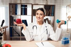 Female doctor sitting at desk in office with microscope and stethoscope. Woman is holding apple and dumbbell. royalty free stock image
