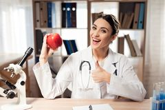 Female doctor sitting at desk in office with microscope and stethoscope. Woman is holding red apple. royalty free stock photography