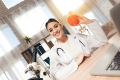 Female doctor sitting at desk in office with microscope and stethoscope. Woman is holding red pepper. stock photo