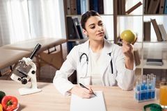Female doctor sitting at desk in office with microscope and stethoscope. Woman is holding yellow apple. royalty free stock photography