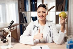 Female doctor sitting at desk in office with microscope and stethoscope. Woman is holding yellow apple. royalty free stock images