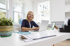 Female Doctor Sitting At Desk Working At Laptop In Office Royalty Free Stock Photo