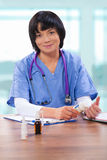 Female doctor sitting at table and holding medical bottle Royalty Free Stock Photo