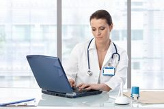 Female doctor sitting at table with laptop Royalty Free Stock Images