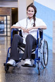 Female doctor sitting on wheel chair Royalty Free Stock Images