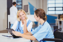 Female doctor sitting on wheelchair while using digital tablet with colleague Royalty Free Stock Photos