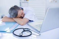 Female doctor sleeping on desk Royalty Free Stock Image