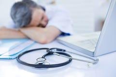 Female doctor sleeping on desk Stock Photos