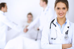 Female doctor smiling on the background with patient in the bed and two doctors Stock Photos