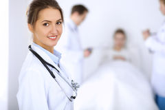 Female doctor smiling on the background with patient in the bed and two doctors Stock Photo
