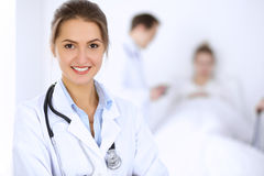 Female doctor smiling on the background with patient in the bed and two doctors.  Stock Photography