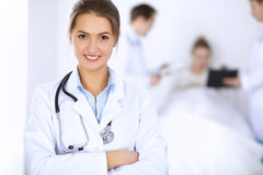 Female doctor smiling on the background with patient in the bed and two doctors Royalty Free Stock Photo