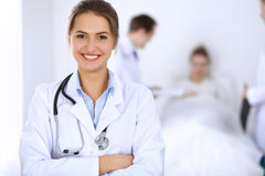 Female doctor smiling on the background with patient in the bed and two doctors Royalty Free Stock Photos