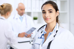 Female doctor smiling on the background with patient and his physician in hospital.  Royalty Free Stock Images