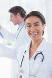 Female doctor smiling at camera while her colleague looking at X-ray Royalty Free Stock Photos