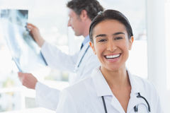 Female doctor smiling at camera while her colleague looking at X-ray Stock Image