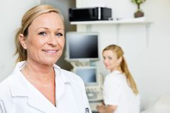 Female Doctor Smiling With Colleague In Background Royalty Free Stock Photos