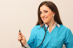 Female doctor smiling with stethoscope in hands Royalty Free Stock Photos